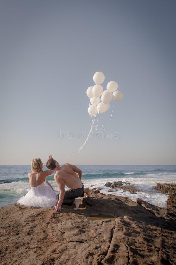 Pares nupciales hermosos jovenes que lanzan los globos blancos en la playa fotos de archivo libres de regalías