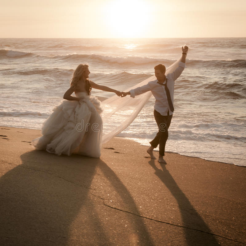 Pares nupciales hermosos jovenes que se divierten junto en la playa imágenes de archivo libres de regalías