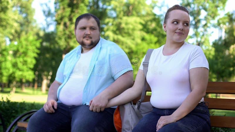 Pares obesos na primeira data, homem que guardam maciamente a mão da amiga, amor e cuidado fotos de stock