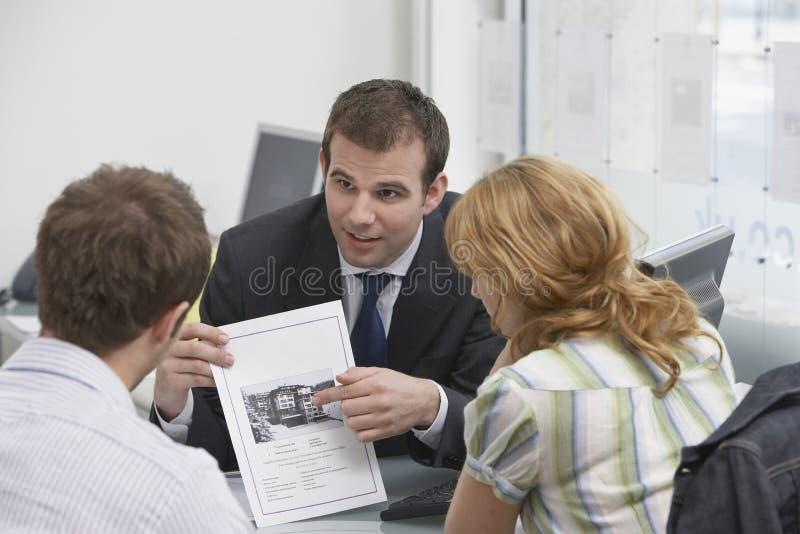 Pares observando o folheto com mediador imobiliário imagens de stock royalty free