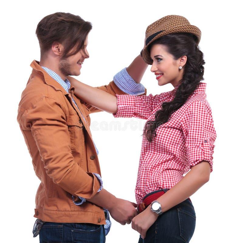 Pares ocasionais com o homem que retira o chapéu da mulher imagens de stock