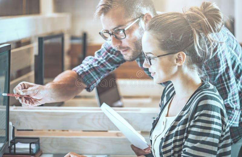 Pares ocasionais do negócio usando o computador no escritório Dois colegas que trabalham junto em um projeto de produto inovativo fotos de stock royalty free