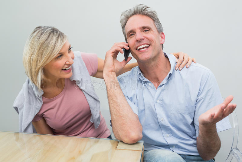 Pares ocasionais felizes usando o telefone celular imagens de stock