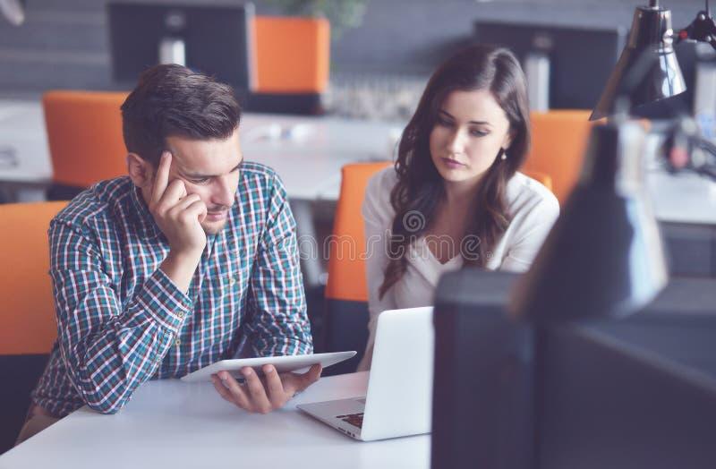 Pares ocasionais novos do negócio usando o computador no escritório Coworking, gerente criativo que mostra a ideia startup nova imagem de stock