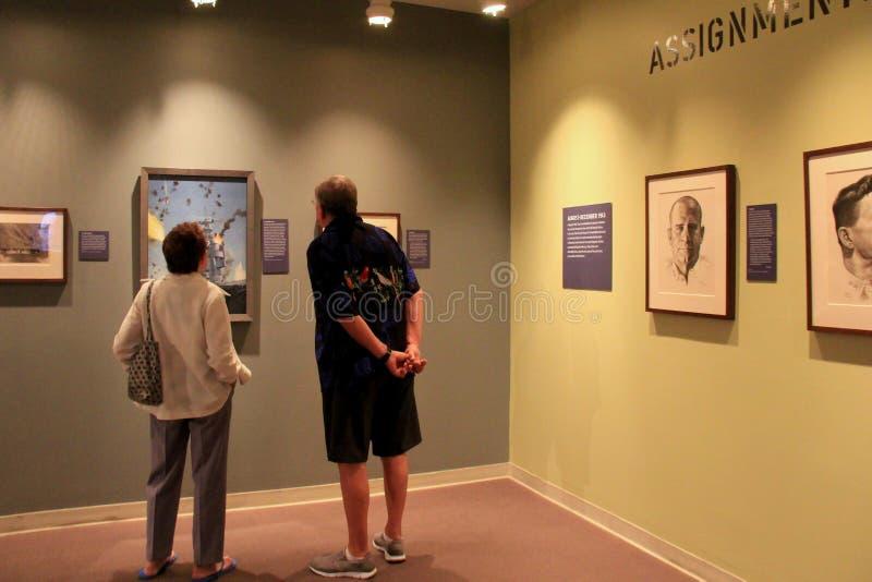 Pares ocasional vestidos que se colocan delante de las imágenes enmarcadas que representan la guerra, museo nacional de WWII, New imagen de archivo
