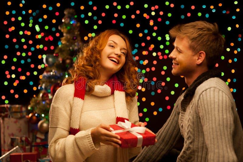 Pares ocasionales sonrientes felices jovenes que hacen un presente foto de archivo libre de regalías