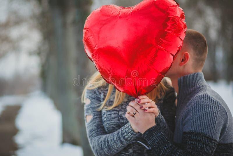 Pares ocultados por el globo en forma de corazón rojo grande imagenes de archivo