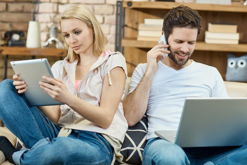 Pares ocupados en casa imagen de archivo libre de regalías