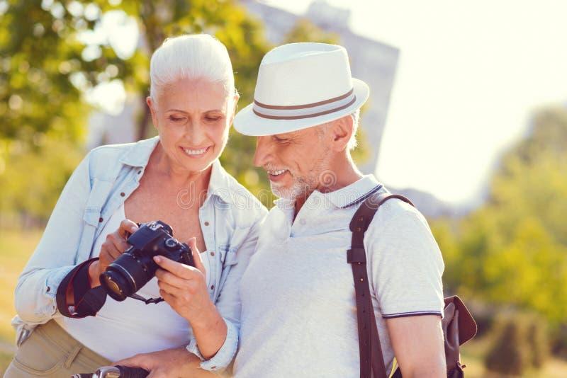 Pares ocupados positivos que olham a foto após o photoshoot da família fotos de stock royalty free