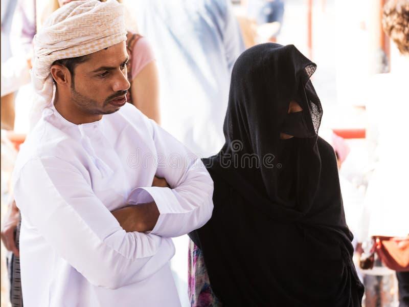 Pares omanenses na roupa tradicional com uma mulher que veste um véu e uma máscara no mercado de sexta-feira em Nizwa foto de stock