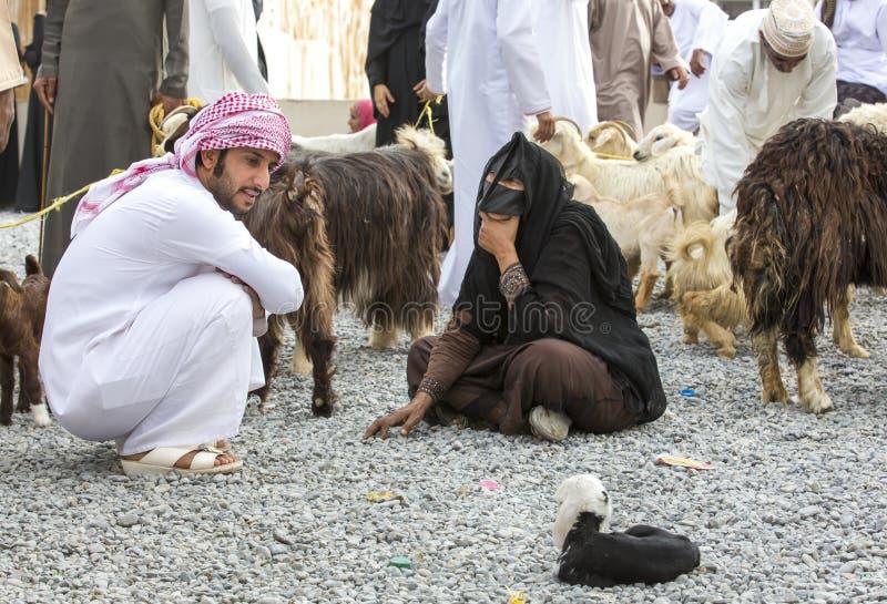 Pares omanenses no mercado da cabra de Nizwa com cabras fotos de stock