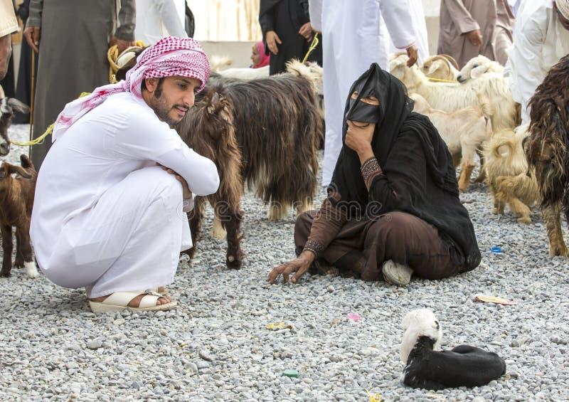 Pares omanenses no mercado da cabra de Nizwa com cabras fotografia de stock
