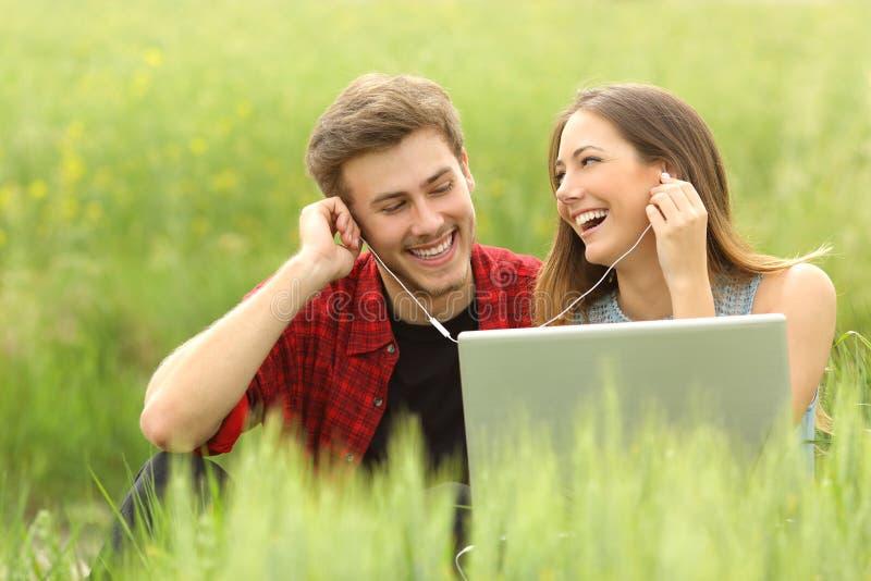 Pares ou amigos felizes que compartilham da música de um portátil imagem de stock royalty free