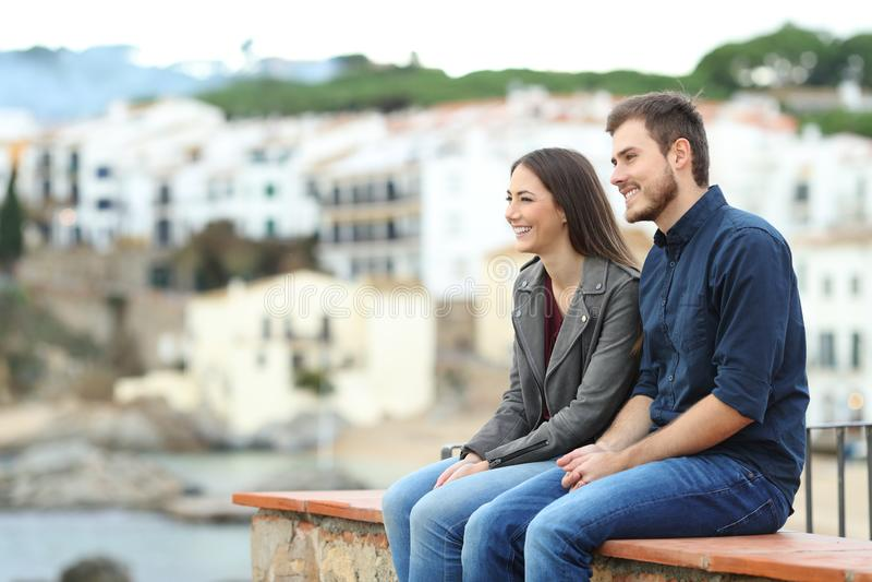 Pares ou amigos que olham afastado em férias em uma cidade da costa fotos de stock royalty free