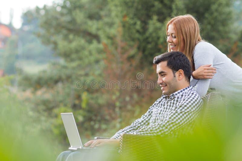 Pares ou amigos que usam o portátil fotografia de stock royalty free