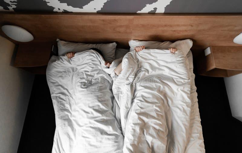 Pares ou fam?lia nova feliz bonita que acordam junto na cama imagem de stock royalty free