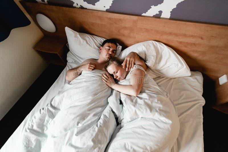 Pares ou fam?lia nova feliz bonita que acordam junto na cama fotos de stock royalty free