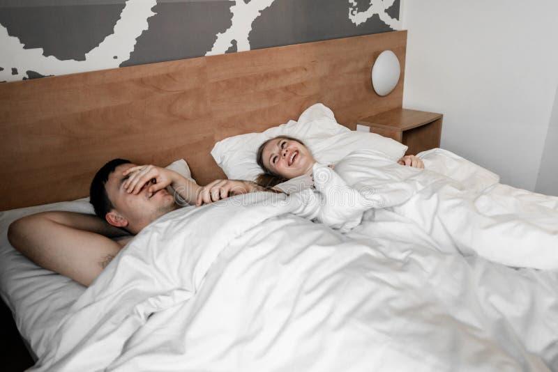 Pares ou fam?lia nova feliz bonita que acordam junto na cama fotos de stock