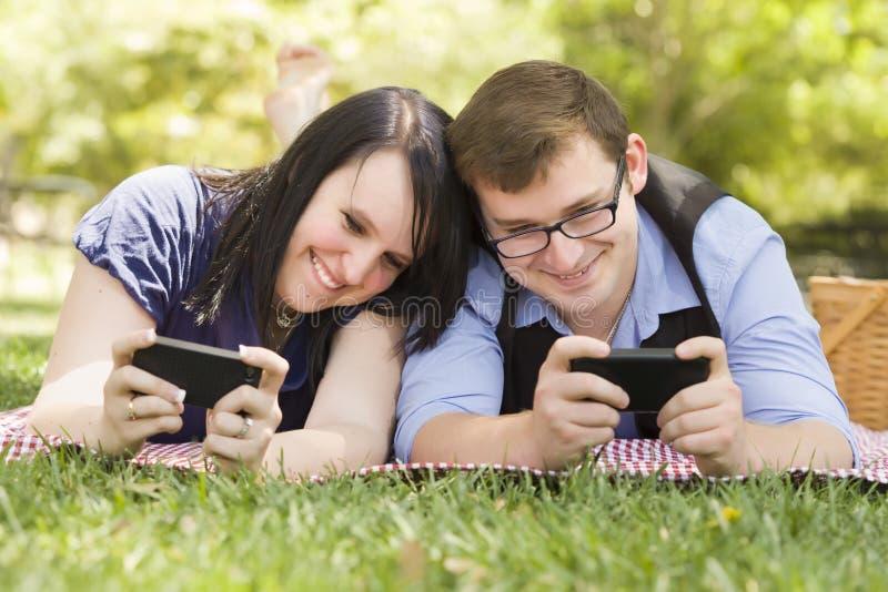 Pares Outdoorsy que Texting em seus telemóveis no parque imagens de stock