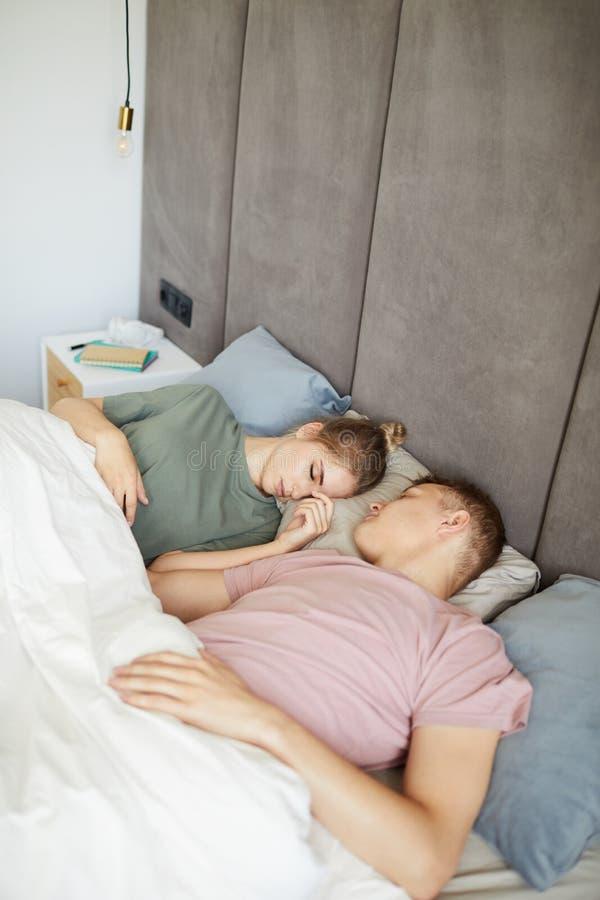 Pares pacíficos jovenes en las camisetas que toman una siesta en cama fotos de archivo