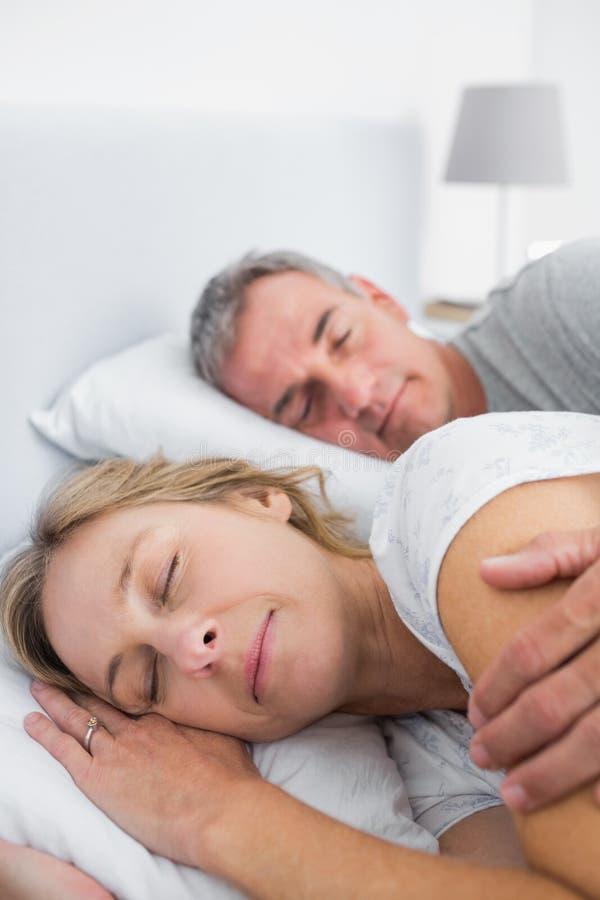 Pares pacíficos que duermen y que cucharean en cama foto de archivo