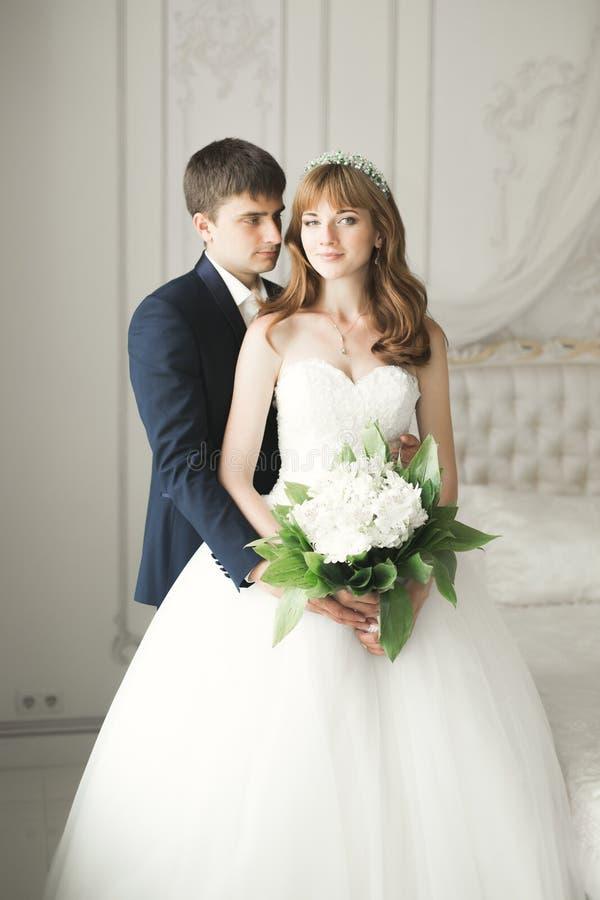 Pares perfectos de la boda que sostienen el ramo de lujo de flores fotografía de archivo libre de regalías