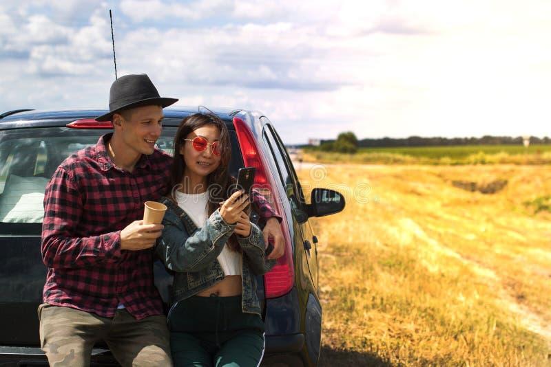 Pares perto da natureza exterior esperta do telefone da posse da mulher da estrada do campo do carro do céu azul fotografia de stock