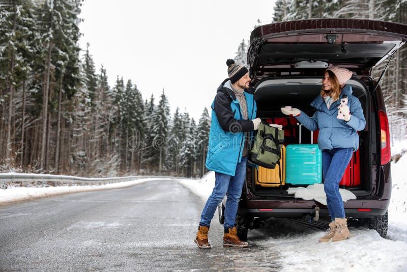 Pares perto do tronco de carro aberto completamente da bagagem na estrada, espaço para o texto foto de stock royalty free