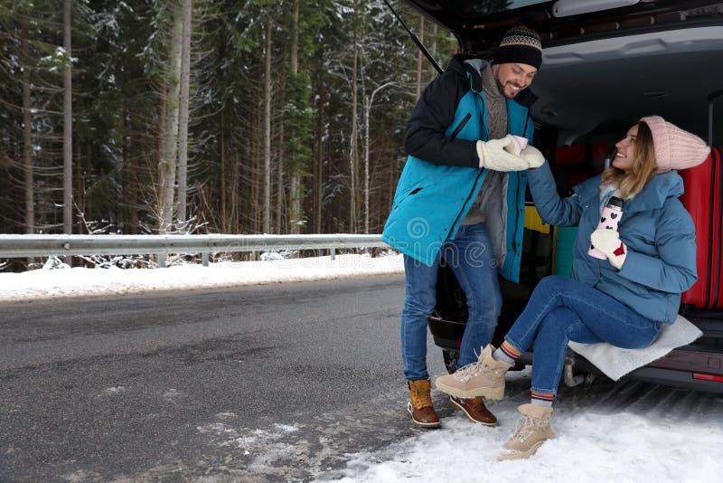 Pares perto do tronco de carro aberto completamente da bagagem na estrada, espaço para o texto Inverno imagem de stock royalty free