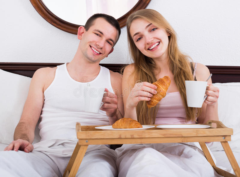 Pares positivos novos que comem o café da manhã saudável imagens de stock royalty free