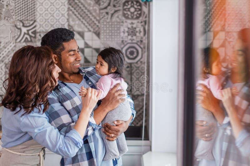Pares positivos novos que jogam com sua criança pequena em casa foto de stock royalty free