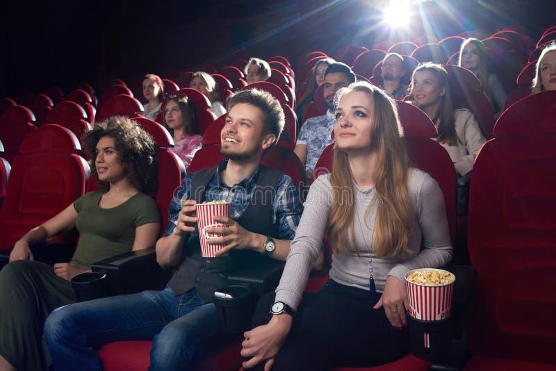Pares positivos que olham o filme engraçado no cinema e que comem a pipoca imagem de stock