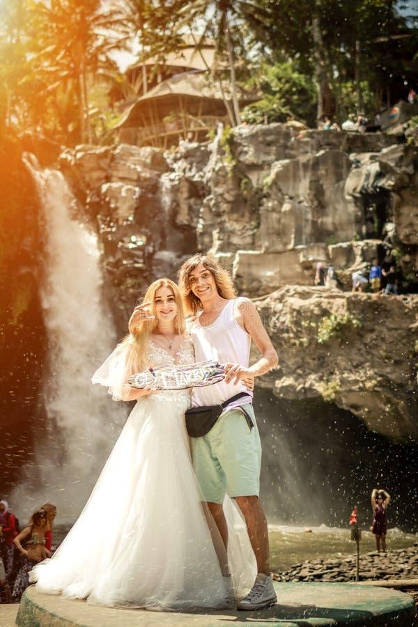 Pares preciosos de la boda contra la cascada en puesta del sol, isla tropical de Bali foto de archivo