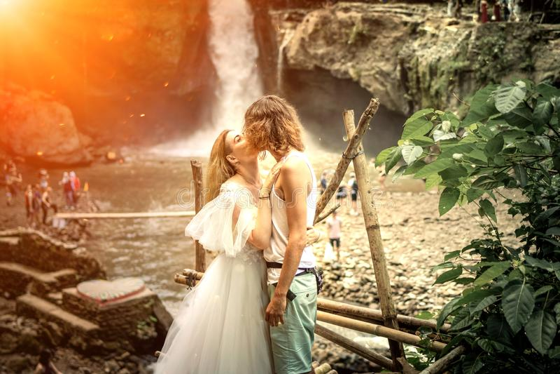 Pares preciosos de la boda contra la cascada en puesta del sol, isla tropical de Bali fotos de archivo