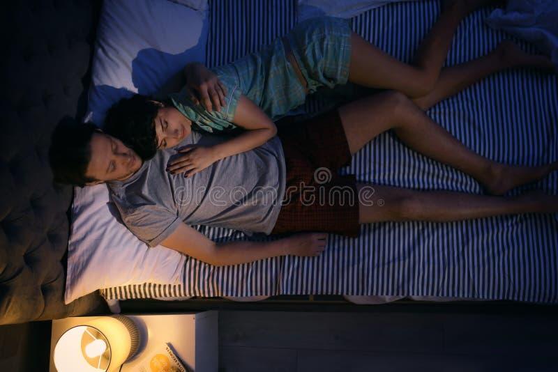 Pares preciosos jovenes que duermen en cama imagen de archivo