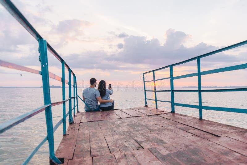 Pares preciosos que se sientan en el embarcadero y que miran en salida del sol fotos de archivo libres de regalías