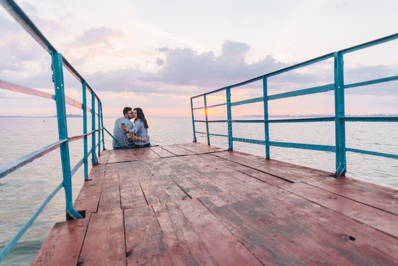 Pares preciosos que se sientan en el embarcadero y que miran en salida del sol foto de archivo libre de regalías