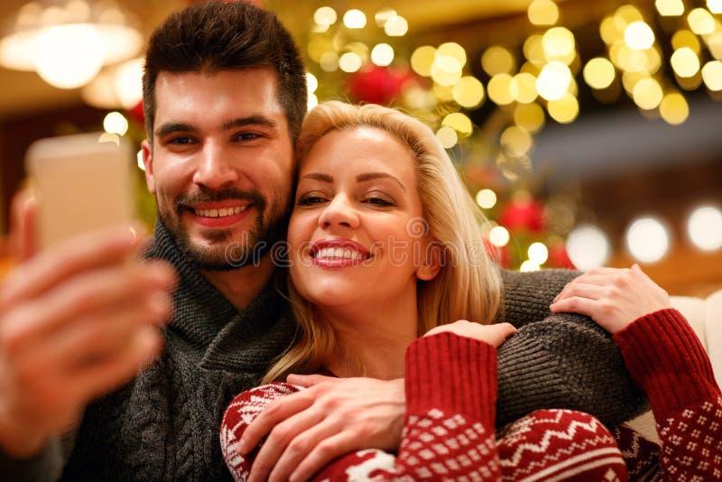 Pares preciosos que toman el selfie con smartphone en la Navidad fotografía de archivo