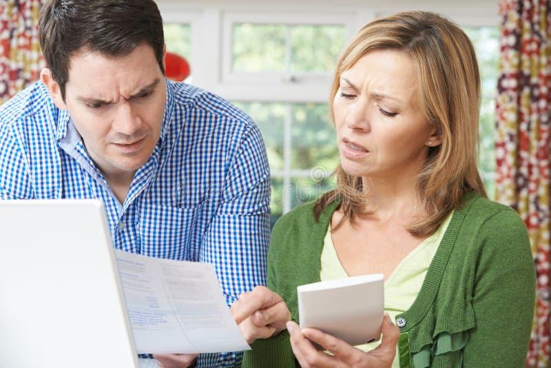 Pares preocupados que discutem finanças domésticas em casa foto de stock royalty free