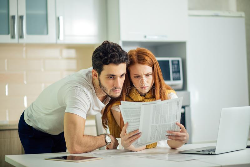 Pares preocupados que pagam suas contas em linha com portátil em casa na sala de visitas fotografia de stock