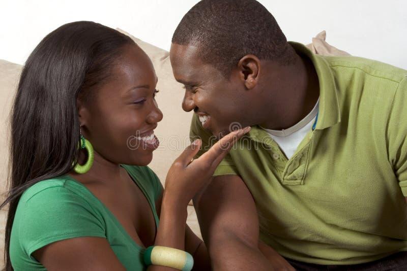 Pares pretos étnicos novos felizes que sentam-se no sofá fotografia de stock