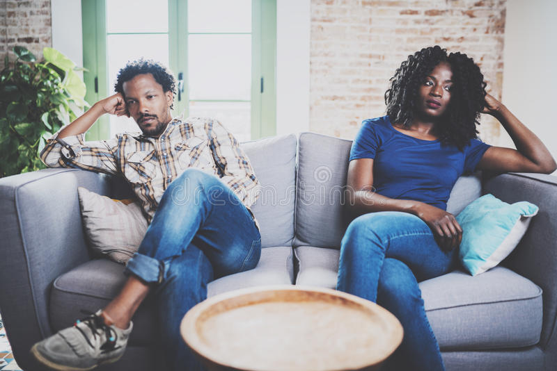 Pares pretos desagradados jovens Homens africanos americanos que discutem com sua amiga à moda, que se está sentando no sofá no s fotos de stock