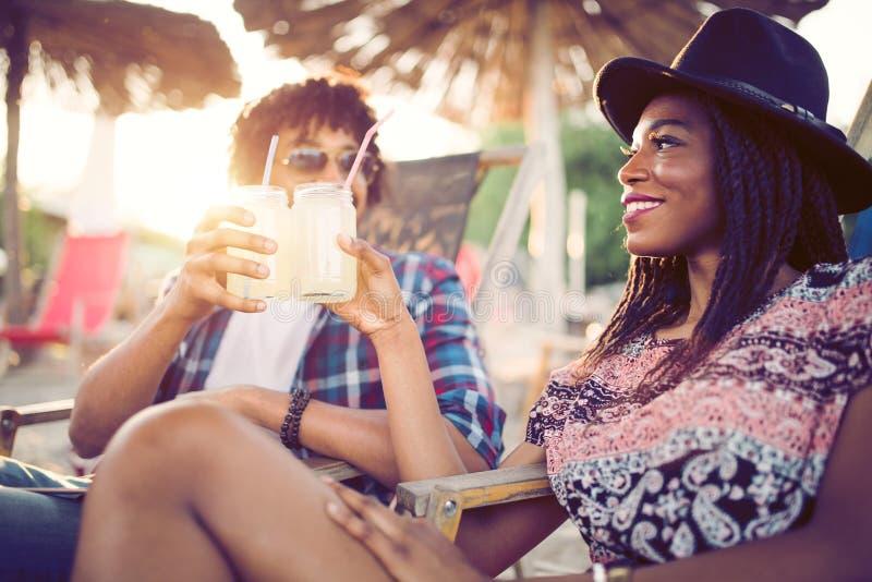 Pares pretos felizes na praia ao relaxar em suas cadeiras de plataforma imagens de stock