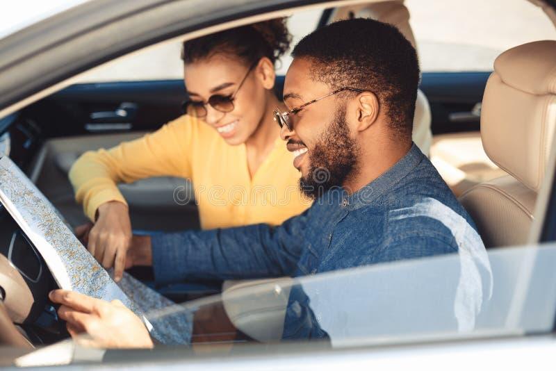 Pares pretos felizes que olham o mapa no carro imagem de stock