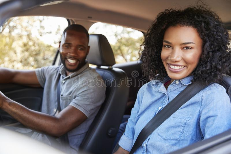 Pares pretos novos felizes que conduzem em um carro que sorri à câmera foto de stock