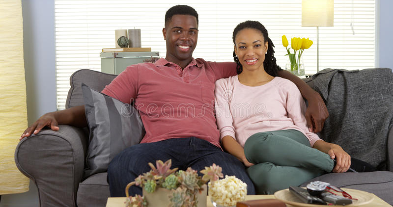 Pares pretos novos felizes que relaxam no sofá que olha a câmera foto de stock royalty free