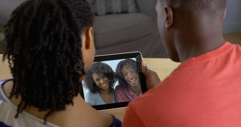 Pares pretos novos que falam aos amigos sobre o bate-papo video do tablet pc fotos de stock