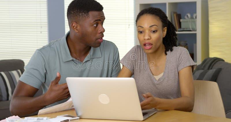 Pares pretos novos virados que discutem sobre contas e finanças com o portátil foto de stock royalty free