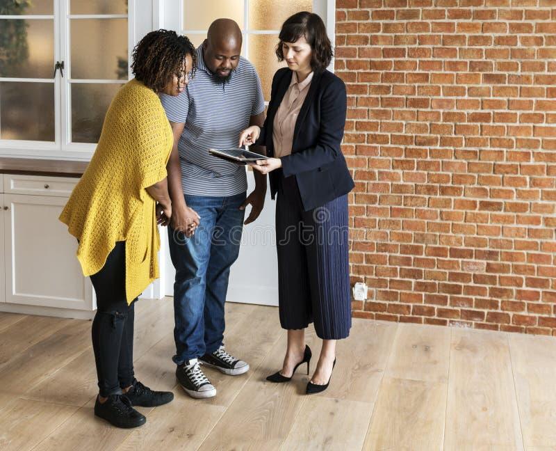 Pares pretos que compram a casa nova que trata o corretor imagem de stock