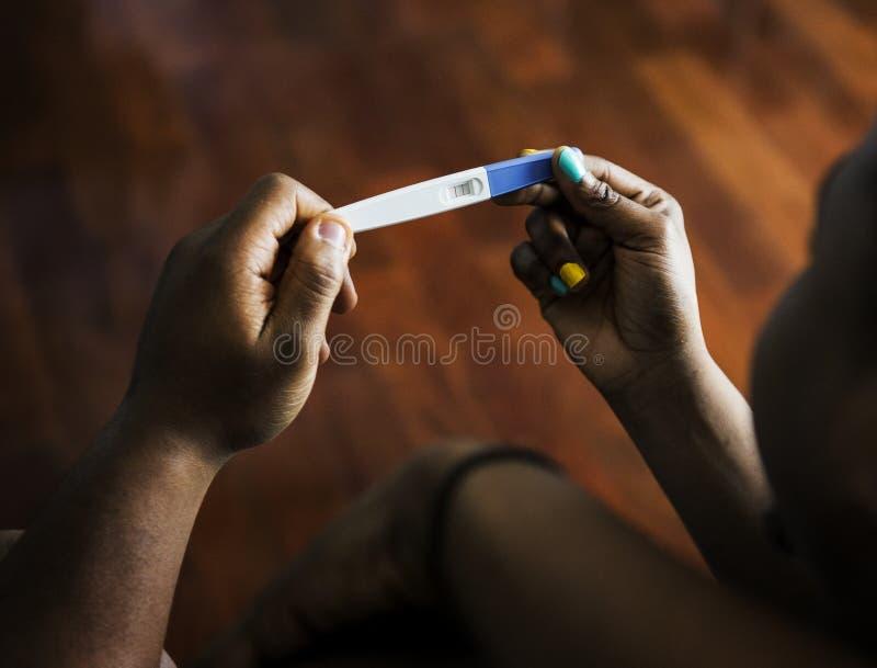 Pares pretos que olham o teste de gravidez fotografia de stock royalty free